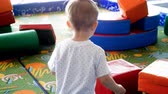4k video of adorable toddler boy playing with big soft blocks on indoor playground at shopping mall