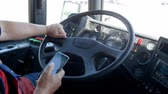 Closeup 4k footage of public bus driver typing message on smartphone and talking by phone. Concept of irresponsible driver and danger on road Stock Footage