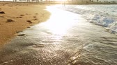 4k video of sea waves rolling over footprints on wet sand on the beach at sunset light