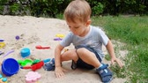 4k footage of cute toddler boy playing in the sandbox on playground at park