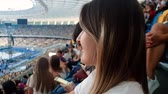 4k closeup video of beautiful smiling young woman with long hair sitting on tribunes of big stadium and watching football match