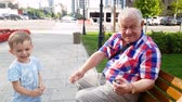 4k video of grandfather with grandson launching toy helicopter on bench at park