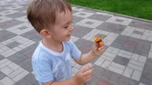 4k video of cheerful smiling toddler boy running holding small toy in park Stock Footage