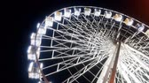 4k video of rotating illuminated ferris wheel in amusement park against night sky