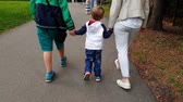 4k video of happy family with little toddler boy holding by hands and walking in park