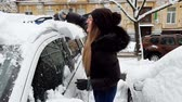4k video of beautiful female driver cleaning her car from snow after blizzard at morning