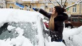 4k video of smiling female driver removing snow from her car at morning after snowstorm