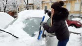 4k footage of smiling young woman cleaning her car from snow before riding to work Stock Footage