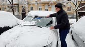 4k footage of young man removing snow from his car at morning before riding to work
