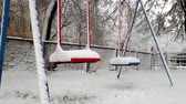 tempestade de neve : 4k footage of empty swings on playground covered in snow swaying by wind