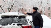 4k footage of young man cleaning his car from snow after snowstorm with telescopic brush