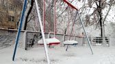 4k footage of swings on playground covered in snow after blizzard at winter. No kids are playing around