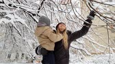 4k video of happy laughing toddler boy with young mother standing under tree covered in snow and shaking its branches. Snow falling on cheerful family Stock Footage