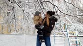 4k video of happy smiling young woman holding her toddler boy and playing with snow at winter park