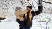 4k video of young mother holding her toddler son and shaking tree branches covered with snow. Family having fun at winter park Stock Footage