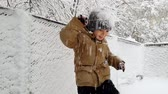 4k footage of cheerful little boy enjoys and playing with snow at winter park