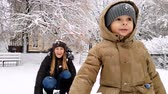 śnieżka : 4k footage of young mother with her toddler son having snowball fight on playground at park