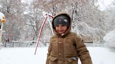 bambini : 4k video of happy smiling toddler boy throwing snowballs on playground at winter park after snow storm
