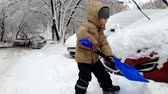 scrapper : 4k footage of little toddler boy sawing car stuck in snowdrift after snow storm. Child digging snow with shovel