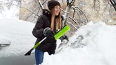 balai : 4k footage of young smiling woman cleaning telescopic brush from snow after removing snow from her car