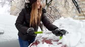 femmes : 4k video of beautiful smiling young woman cleaning car windshield from snow with brush