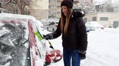 femmes : 4k video of beautiful smiling young woman cleaning her car from snow with telescopic brush