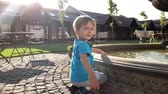 bambini : 4k video of adorable toddler boy touching water in fountain at park