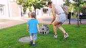 femmes : 4k footage of happy smiling toddler boy with young mother walking in park and looking in toy wooden house
