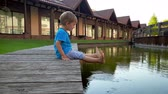 bois : 4k video of chererful smiling toddler boy sitting on the riverbank and holding feet in water of small canal at european town