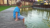 femmes : 4k footage of adorable toddler boy sitting on the riverbank and dipping his feet in water. Child moving legs and splashing water