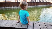 femmes : 4k video of chererful smiling toddler boy sitting on the riverbank and holding feet in water of small canal at european town