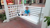 conforto : 4k footage of toddler boy seating on the bench swing on city street Vídeos