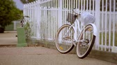 Old White Bicycle Standing Beside Fence - Color Graded 4K Resolution Стоковые видеозаписи