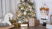 sallanan : 4K footage of New Year tree decorated with present boxes and gifts, rocking horse and nutcracker
