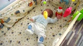 cot : Happy smiling baby lying in the crib and play with music carousel toy.