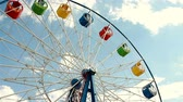 color wheel : Underside view of a ferris wheel over blue sky Stock Footage
