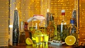 The range of alcoholic tinctures in the bar on the table near the window with blinds and a garland Стоковые видеозаписи