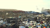 Large garbage dump waste with smoke at sunny day