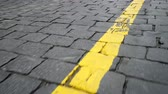 дорожный знак : Yellow line on a road paved with black stone blocks