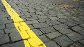 Yellow line on a road paved with black stone blocks