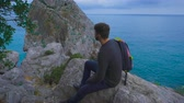 ninhada : Young hipster guy sitting on the rock mountains near sea, man with a rucksack on his back Stock Footage