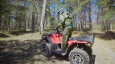 all terrain vehicle atv : Autumn forest. The man in a special form on the ATV. The racer rides on the wood the racing quad bike. Stock Footage