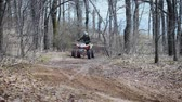 all terrain vehicle atv : Sunny day in the autumn wood. The racer leaves from abrupt turn on the quad bike. The man passes on forest off road terrain.