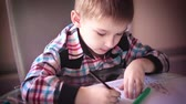 holding : Little boy sitting at table and drawing with colored pencils Stock Footage