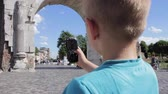 Boy making mobile photo of ancient city