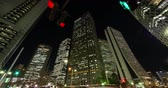 high rise buildings : Urban Skyline in Shinjuku Tokyo at Night (tilt down) Stock Footage