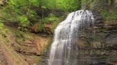 denge : Beautiful waterfalls where water cascades or descends a series of rock steps with scenic background of rock formation and trees Stok Video