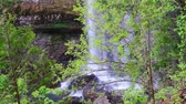 denge : Water plunges down to blocks of rocks at the base of a waterfall with green trees in the foreground Stok Video