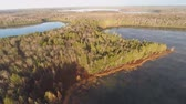 Aerial video over a Northern Wisconsin lake in late fall.  The leaves are off the trees and the calm water of the small lake beautifully reflects the clouds. Dostupné videozáznamy