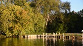 причал : Across the river the leaves are changing color of a boat launch and fishing dock.  Fox River, Wisconsin.